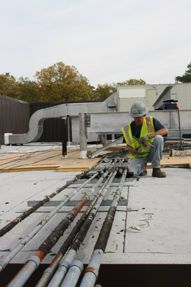 In this photo, a construction crew member works on changing the piping to the energy towers on the Earl Gregg Swem Library roof. These updates will make room for an additional tower to will accommodate the new energy needs of the future ISC 3.  BAILEY KIRKPATRICK / THE FLAT HAT