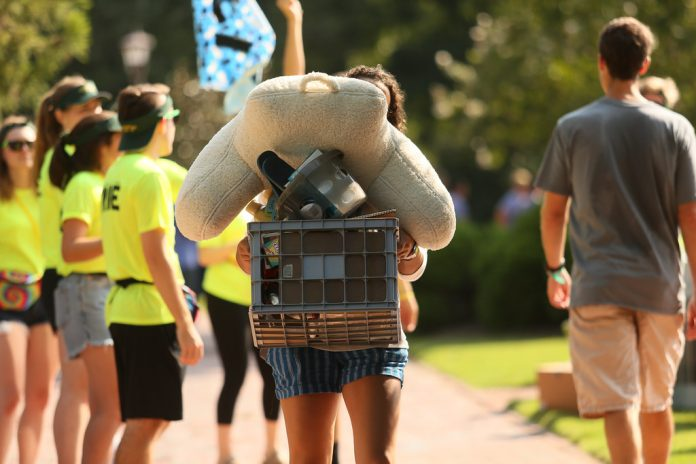 Photograph of student moving in during orientation, with orientation aides behind them